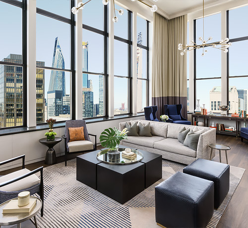 large living room with beige couch and accent chairs and windows overlooking the city