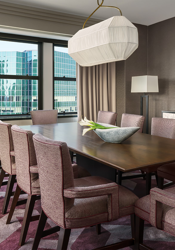 brown rectangular table with pink accent chairs