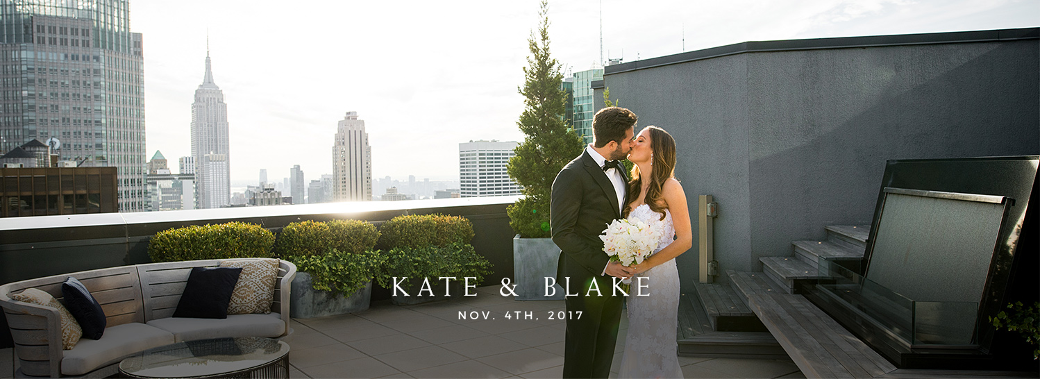 bride and groom kissing on rooftop deck with the city in the background