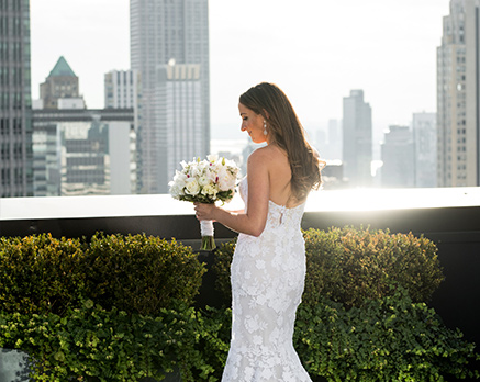 bride holding her flower bouquet is posing for a picture with the city in the background