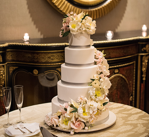 closeup of five tiered wedding cake with flowers going along the tiers