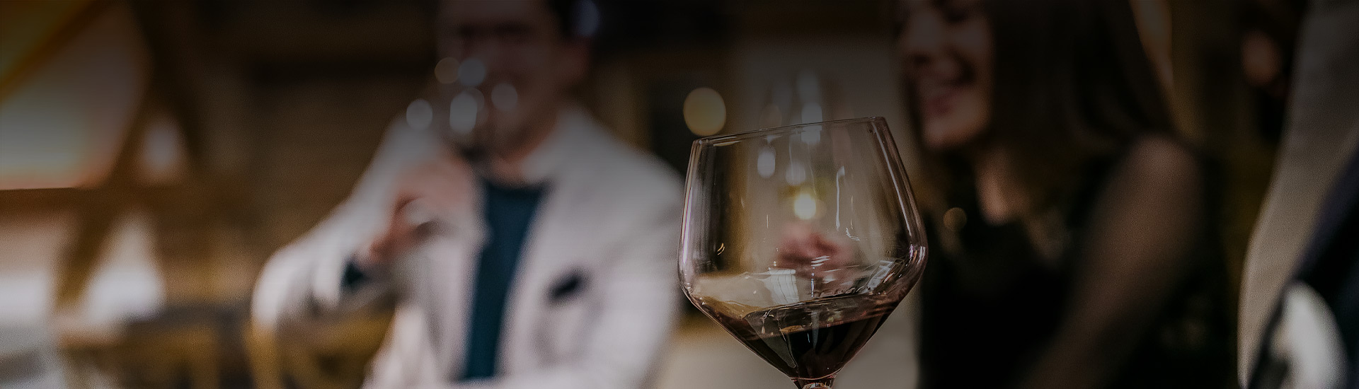 glass of wine with people blurred in background