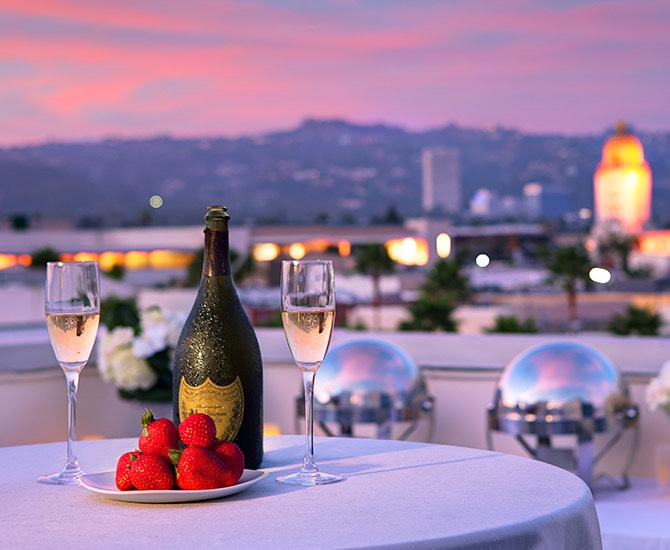 table on rooftop set with champagne and strawberries overlooking city at sunset