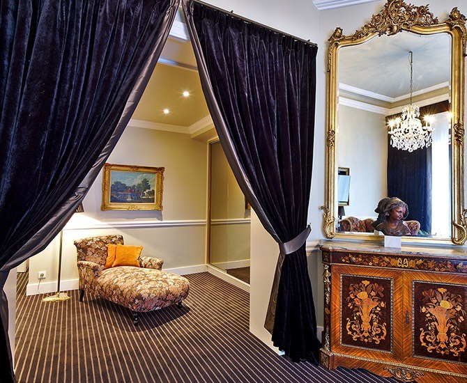 black curtains draped to open up room with chair and room with mirror