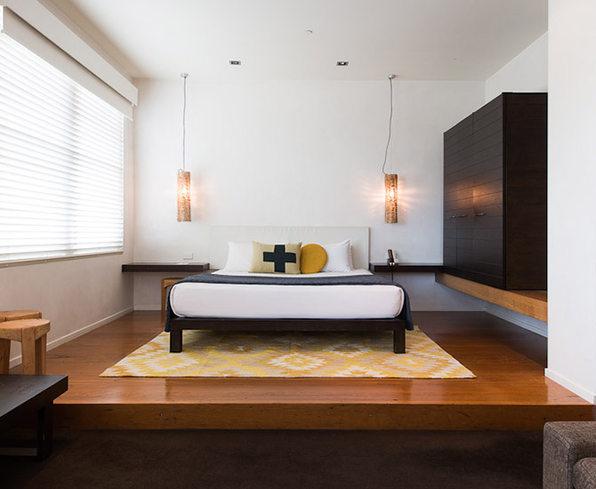 white bed on yellow rug in wooden floor room