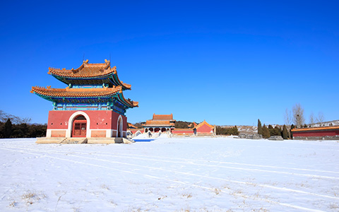 temple styled building with surrounding land masked in snow