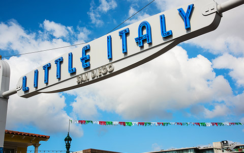 white sign with blue letters reading little italy