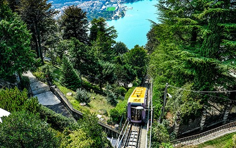 cable car running up a mountain over a blue lake