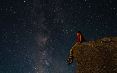 person sitting on ledge of a rock looking up at the stars
