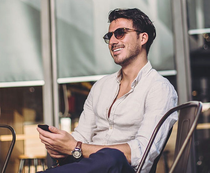 man in chair outside wearing sunglasses and smiling