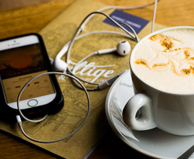 closeup of a table that has an Iphone with headphones and a cappuccino