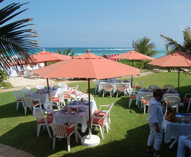 outdoor seating under orange umbrellas with view of water