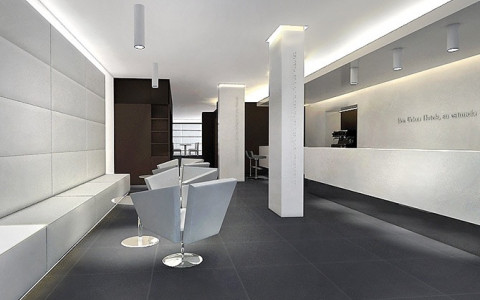 white lobby area with dark grey floors, seating area and desk area by wall