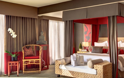 canopy bed with red and brown curtains and a bench at the foot of the bed