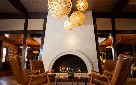 spherical chandeliers over seating area by fireplace