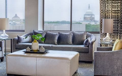 grey sofa and armchairs with white ottoman by window looking out to dc