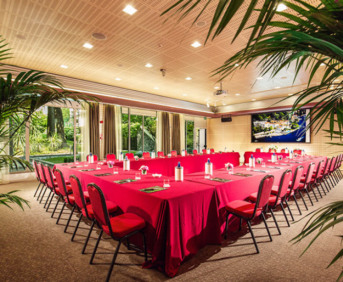 tables set up in rectangular shape with red tablecloth