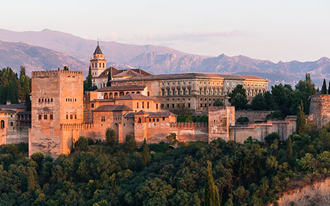 view of the alhambra surrounded by trees and mountains