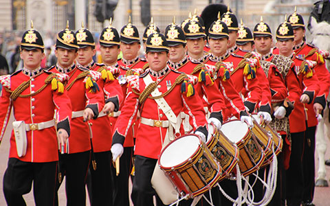 men marching with drums in red uniforms at palace