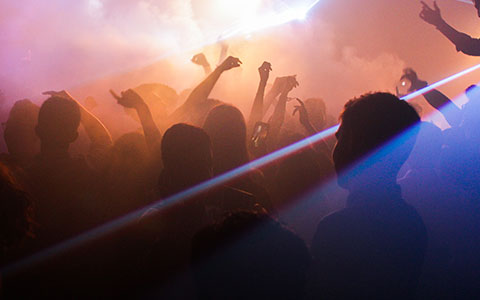 people dancing in nightclub with lights and fog