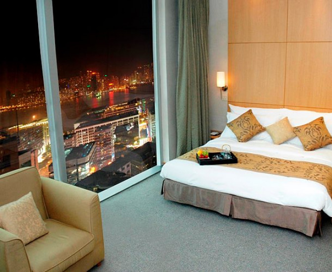 bed with tray on it and floor to ceiling window with view of hong kong at night