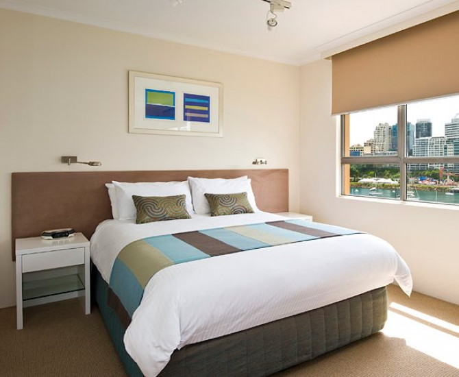 white bed with striped blanket and view of sydney outside window