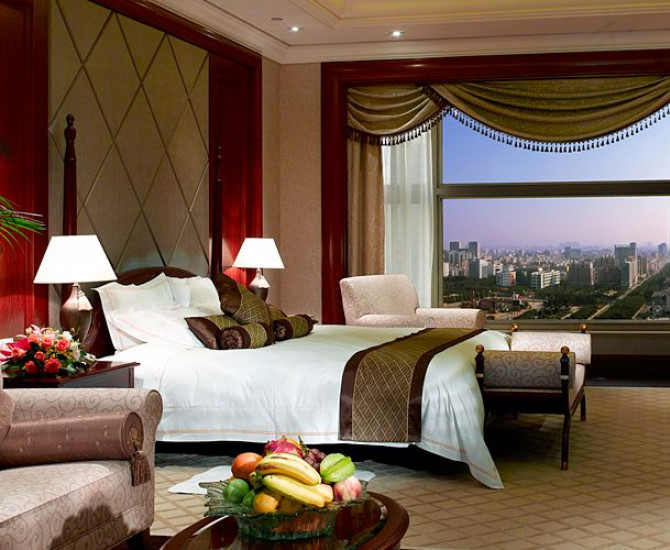 white bed with dark gold and red pillows and blanket in room with view of the city