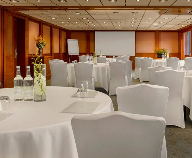 conference room set up with tables and chairs in white tablecloth, flower and white wine bottles on center of tables, and they are all facing towards a screen in the back of the room
