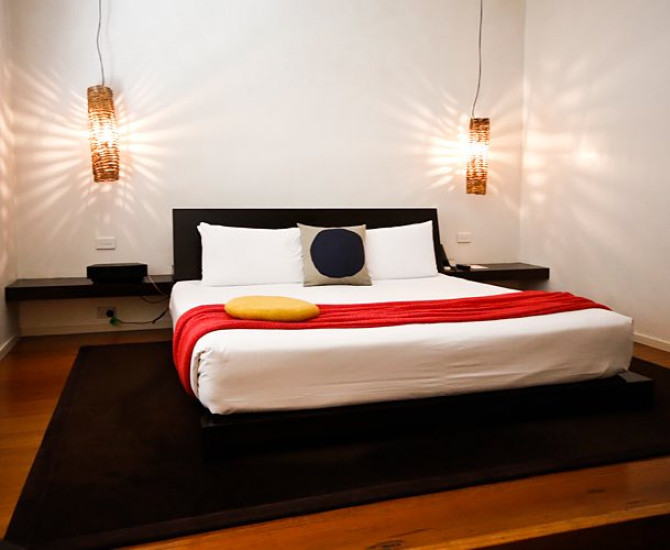 wooden floor with a black carpet underneath a white bed and a red blanket over it