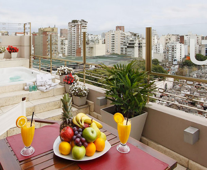 fruit platter and two orange juices set up on a table in outdoor balcony with a jacuzzi and flowers in pots overlooking the city