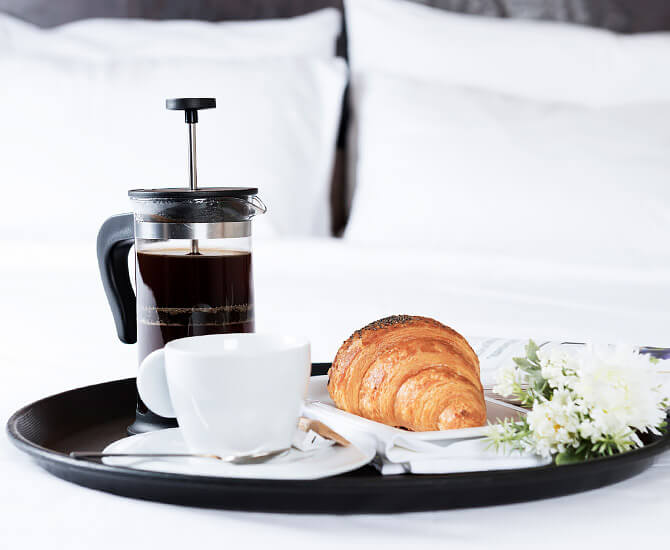 close up view of a tray with coffee, croissant and flowers sitting on a bed with white linens