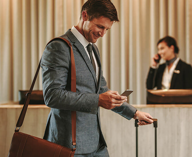 business man checking into a hotel with a shoulder bag and luggage looking at his cell phone