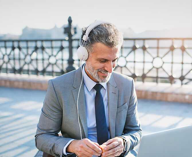 man with grey hair and suit wearing headphone sitting outside