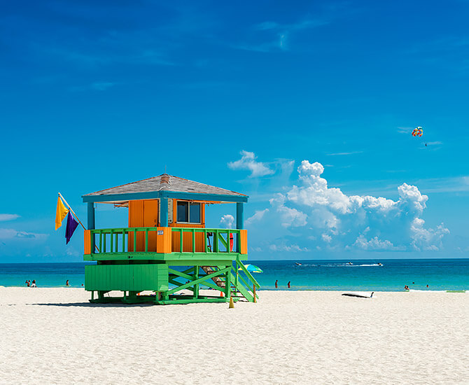 white sand beach with blue skies and colorful lifeguard stand