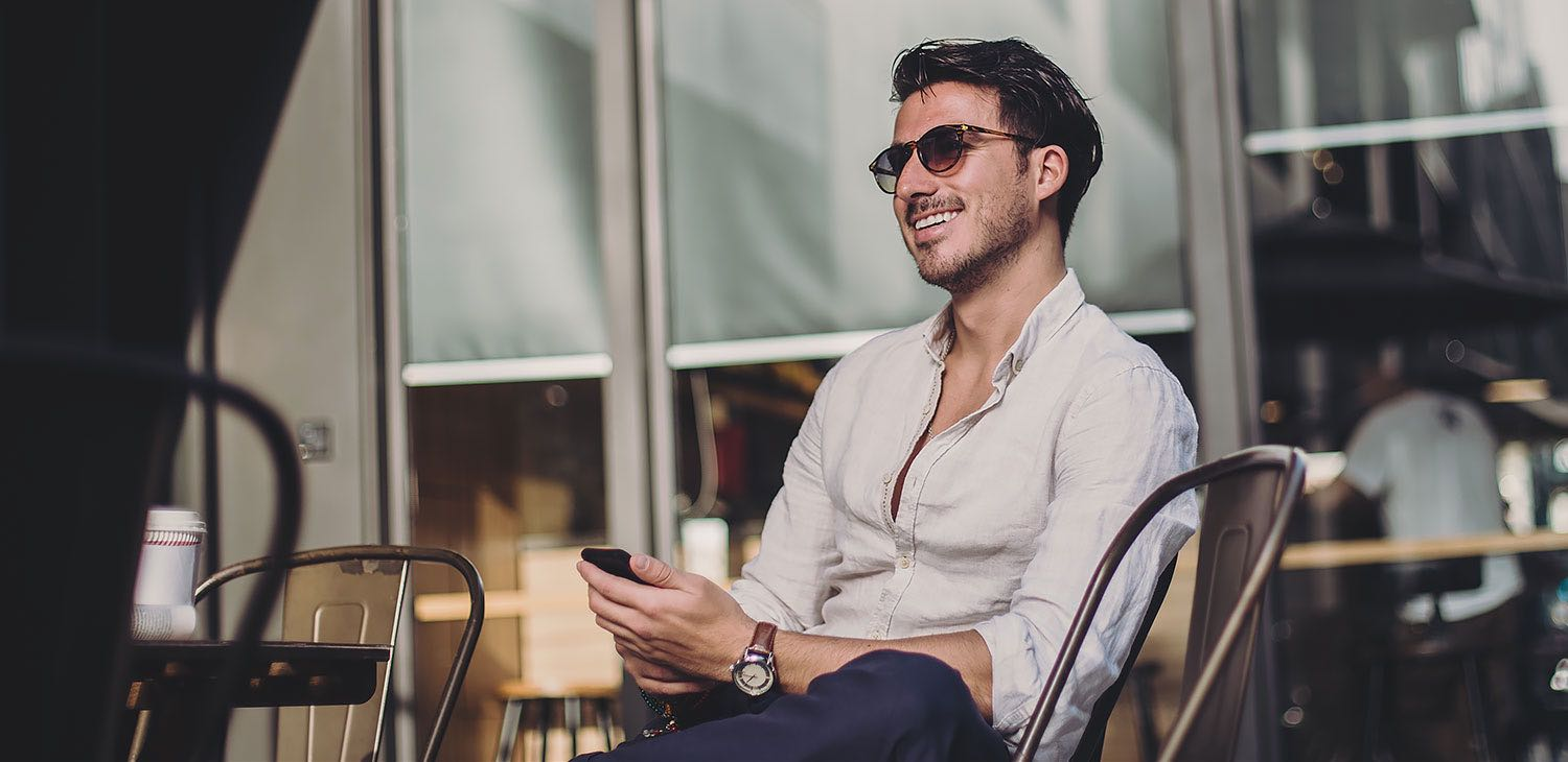 Man seated outside smiling with sunglasses on