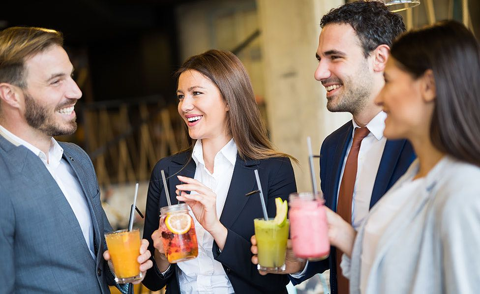 Group of business people holding different color cocktail drinks