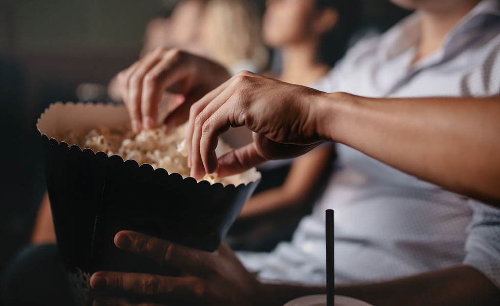Close up of hands grabbing pop corn