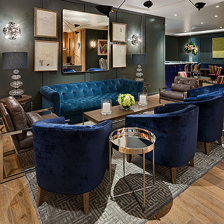 Living space with blue velvet seating chairs, accent rug, wooden table & grey wall