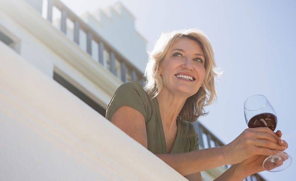 Woman enjoying glass of wine as she looks out of balcony