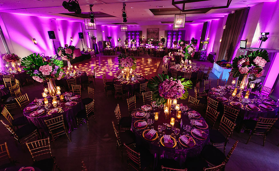 Event space with pink lighting and tables set up for reception