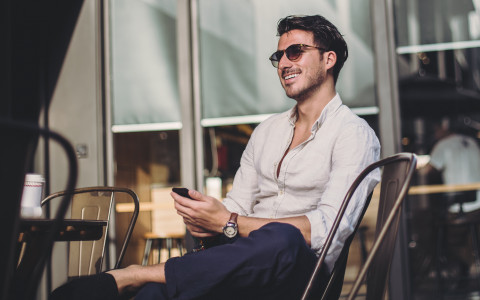 Man with sunglasses smiling with phone in hand