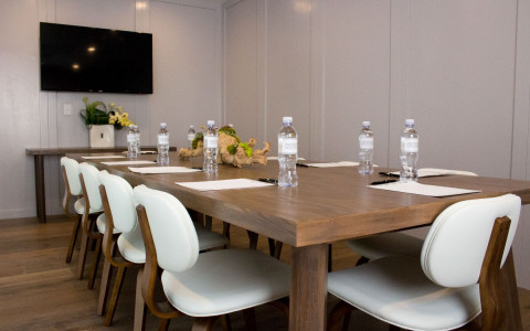 Long wooden meeting table with cushioned white chairs