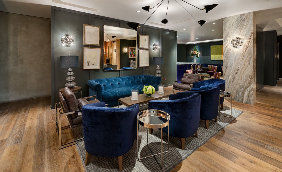 Living space with blue velvet seating chairs, accent rug, wooden table & grey wall  Inset