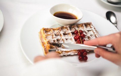 Close up of knife cutting into waffle