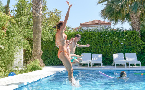 Women jumping into swimming pool