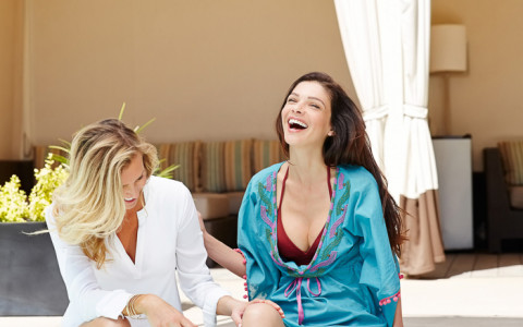 Two women laughing at the edge of pool