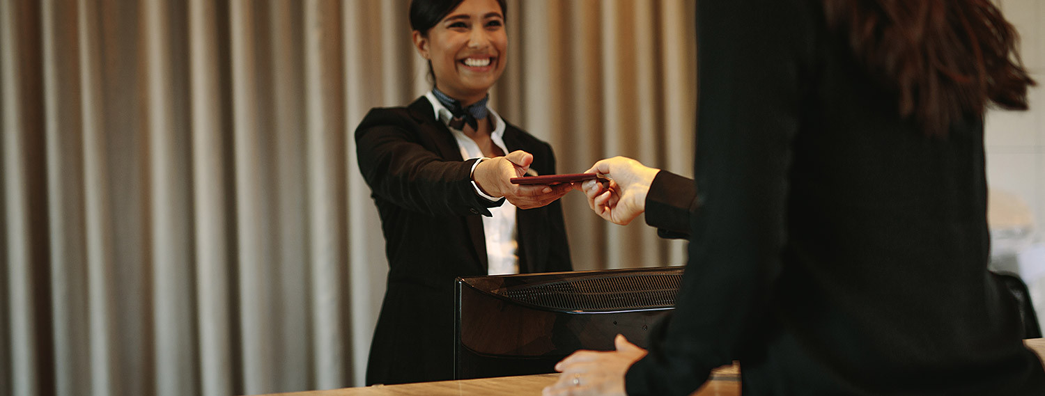 woman handing key card to guest