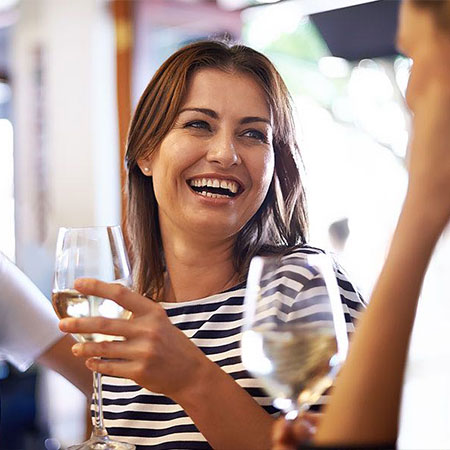 Close up of woman holding glass of wine and laughing