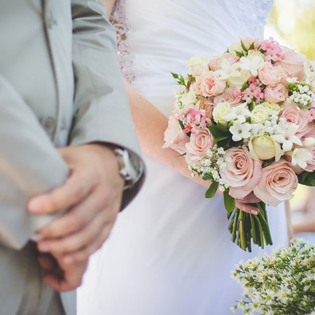 Close up of bride holding bouquet next to groom