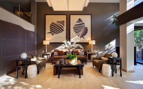 Lobby area with brown couches, wooden coffee table & large abstract shell paintings